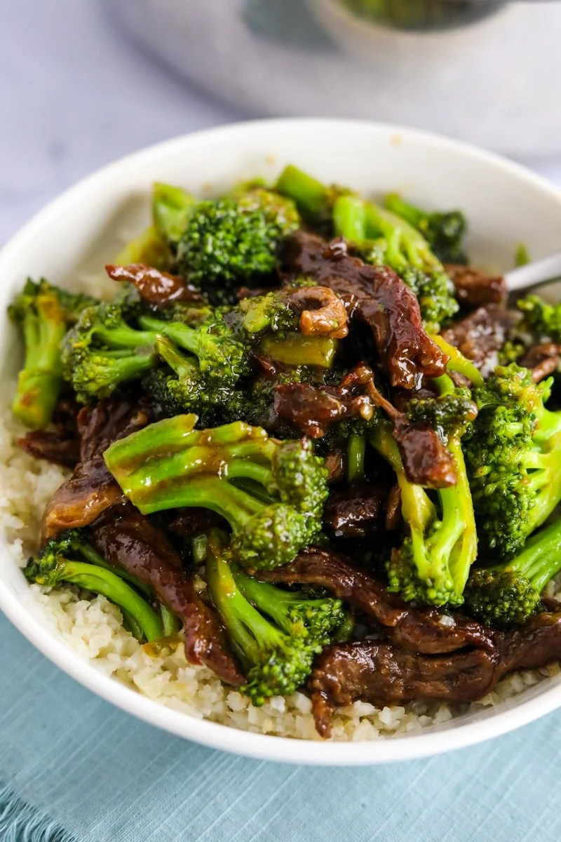 beef and broccoli in a bowl over cauliflower rice