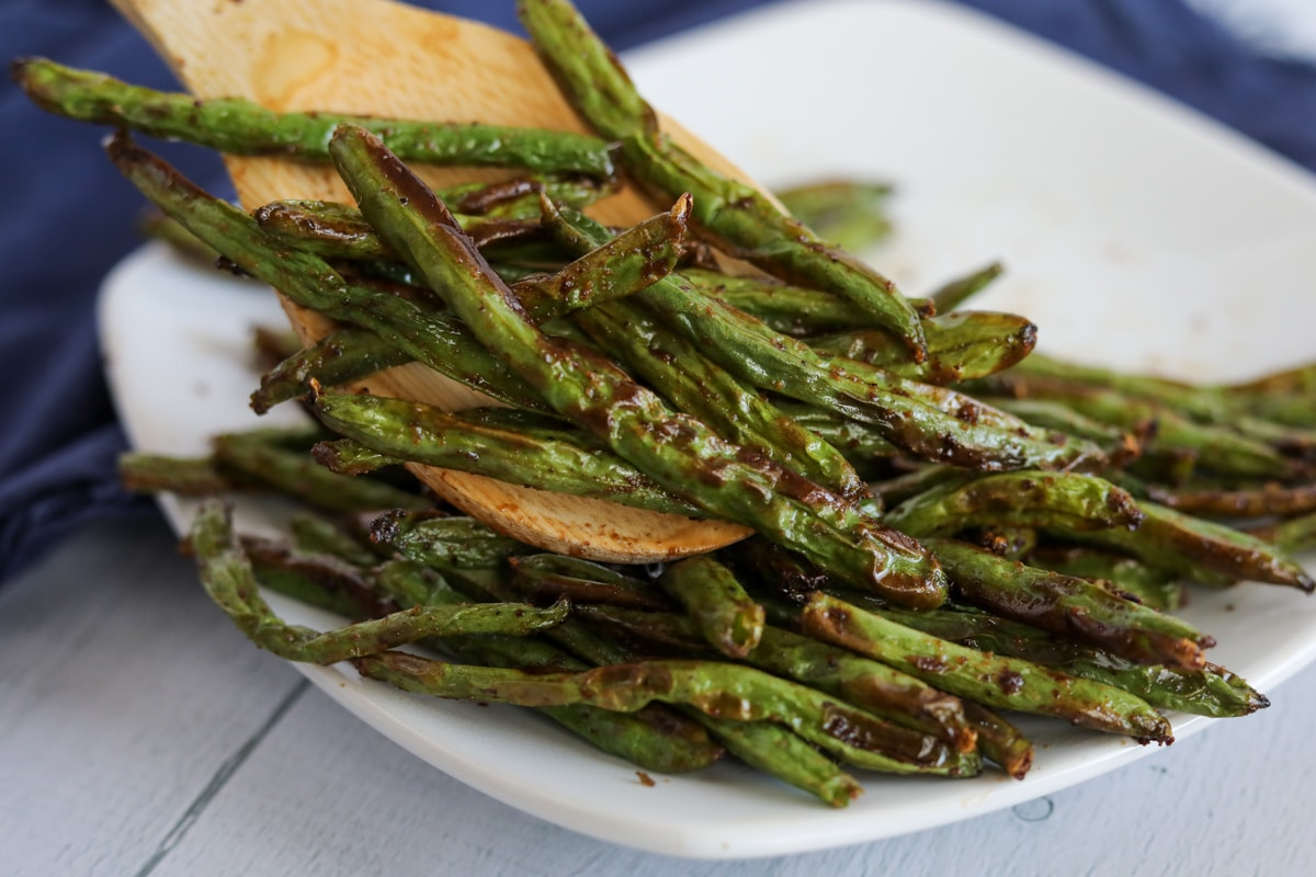 Roasted green beans on a plate with a wooden spatula.