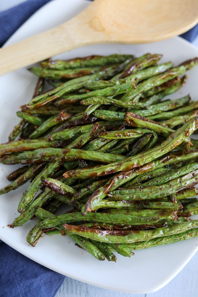 Roasted green beans on a white plate.
