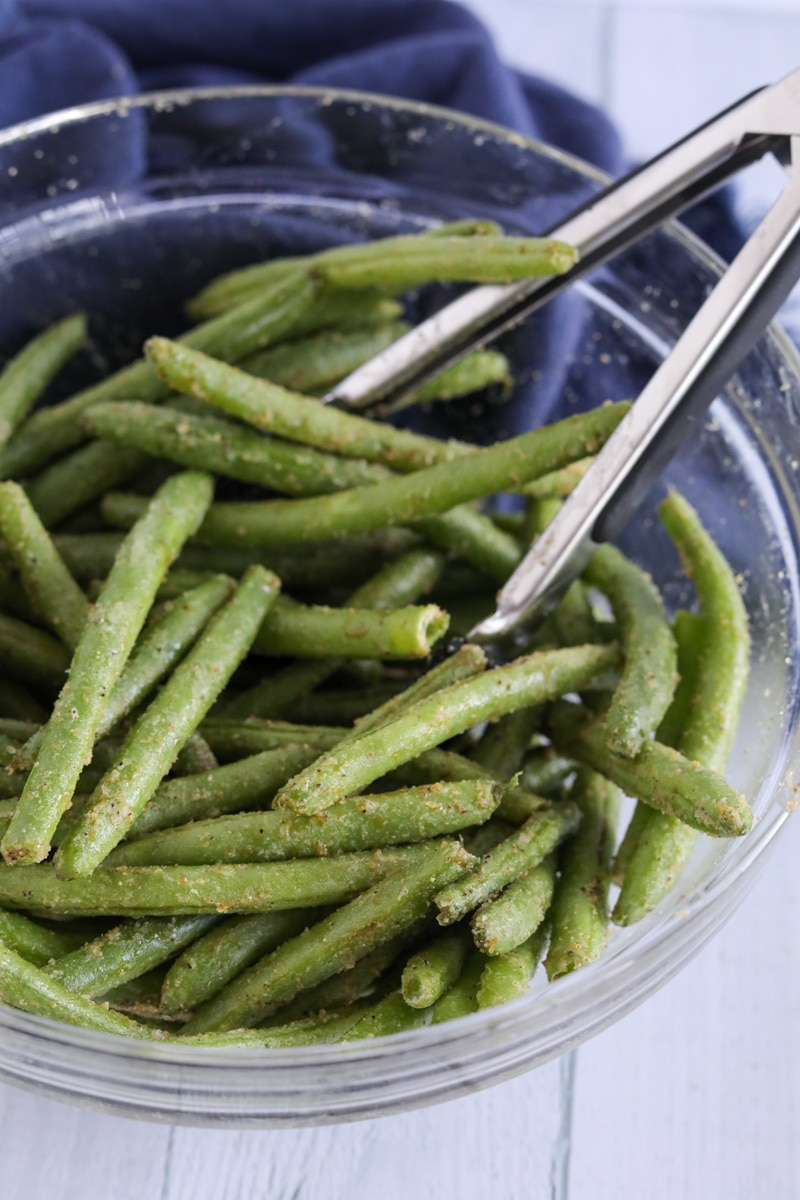 Green beans coated with seasonings in a clear gladdest bowl