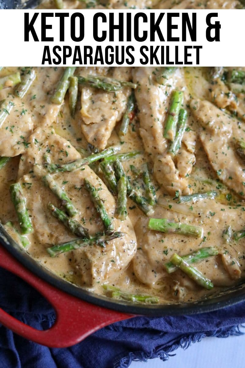 chicken breasts in a creamy cheese sauce with asparagus in a red cast iron skillet