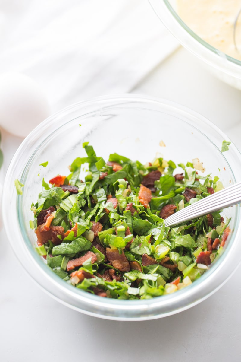 chopped spinach leaves, bacon, peppers and onions in a clear bowl