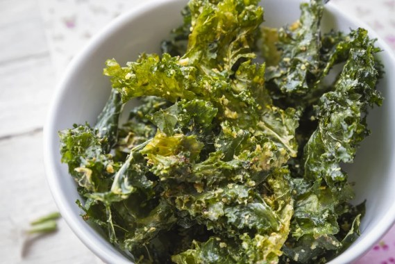 Close up color photo with delicious kale chips on white bowl, ready to enjoy a gourmet snack.