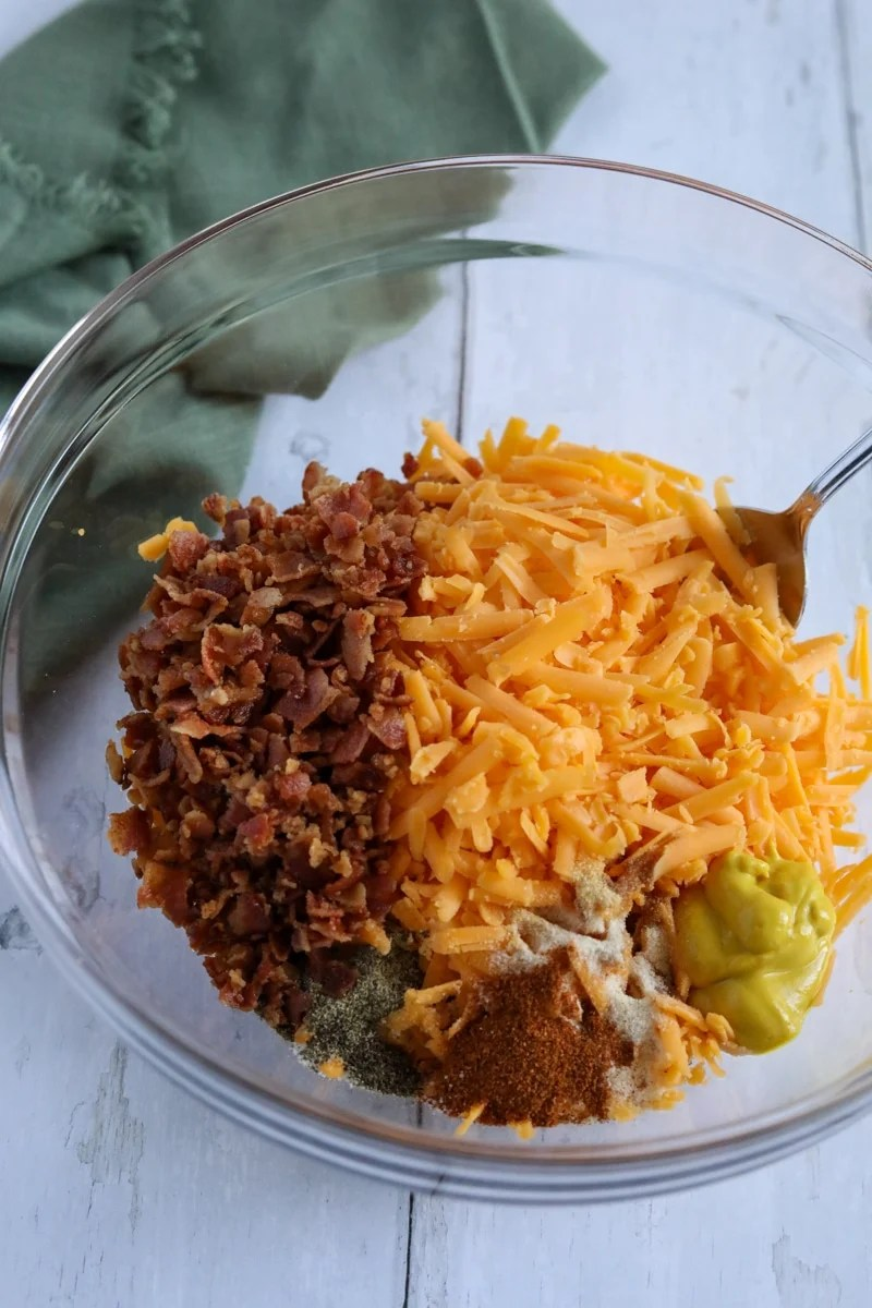 ground beef, cheese, seasoning and bacon in a bowl