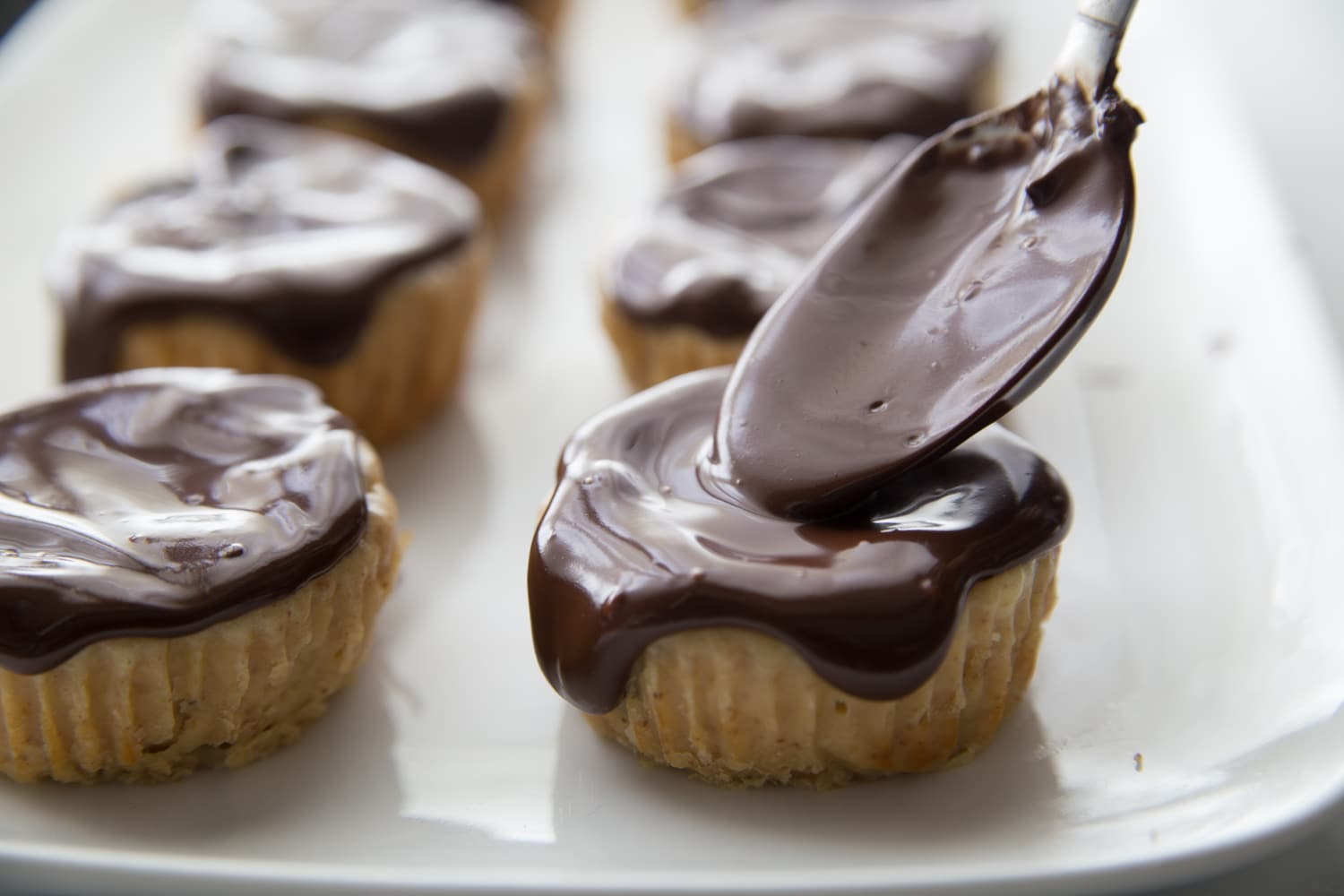 chocolate sauce being spooned over mini cheesecakes