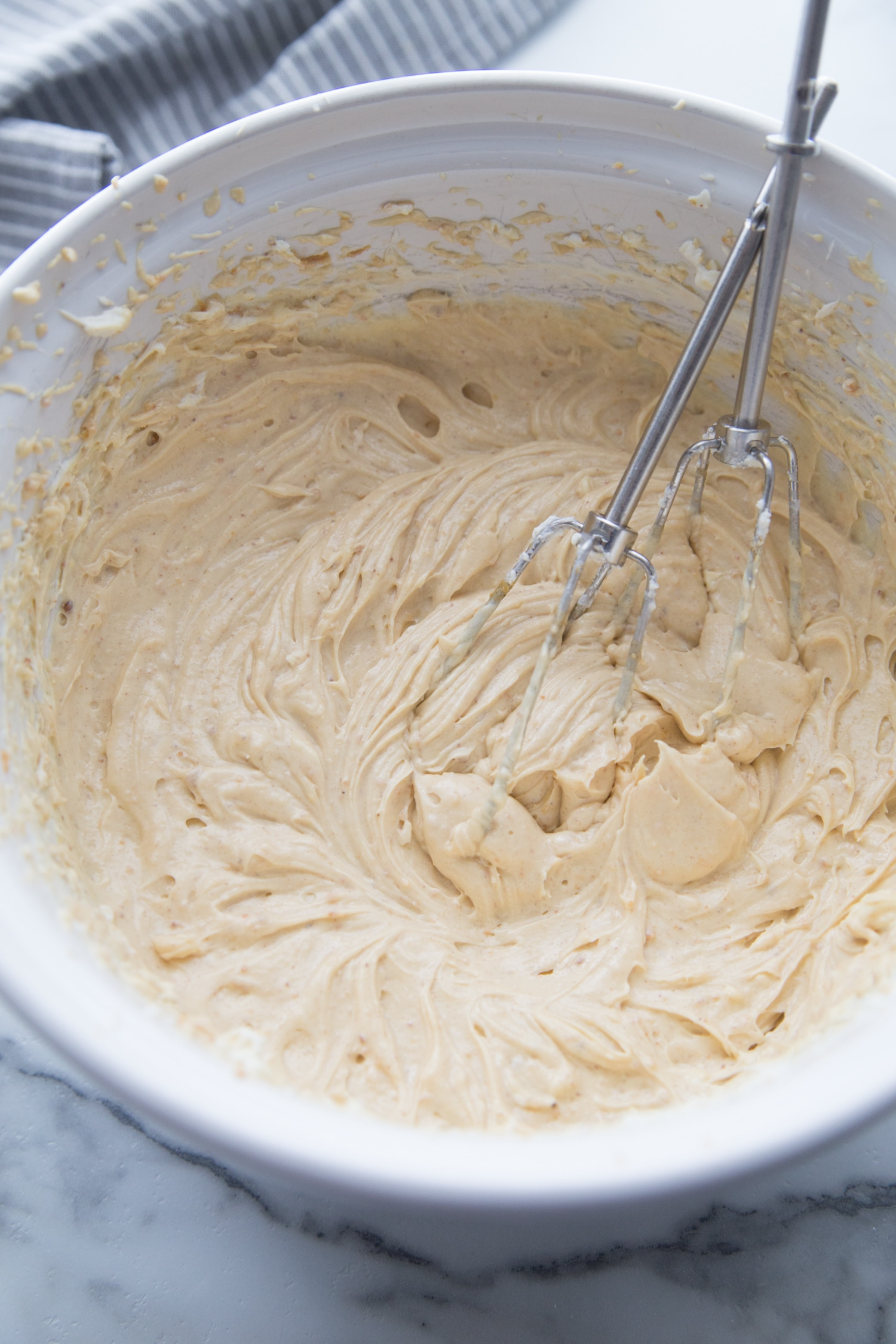 cheesecake batter mixed in a white bowl with two whisks