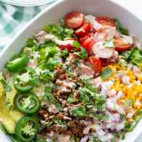 healthy keto taco salad recipe in a bowl with tomatoes, lettuce, ground beef, and cheese