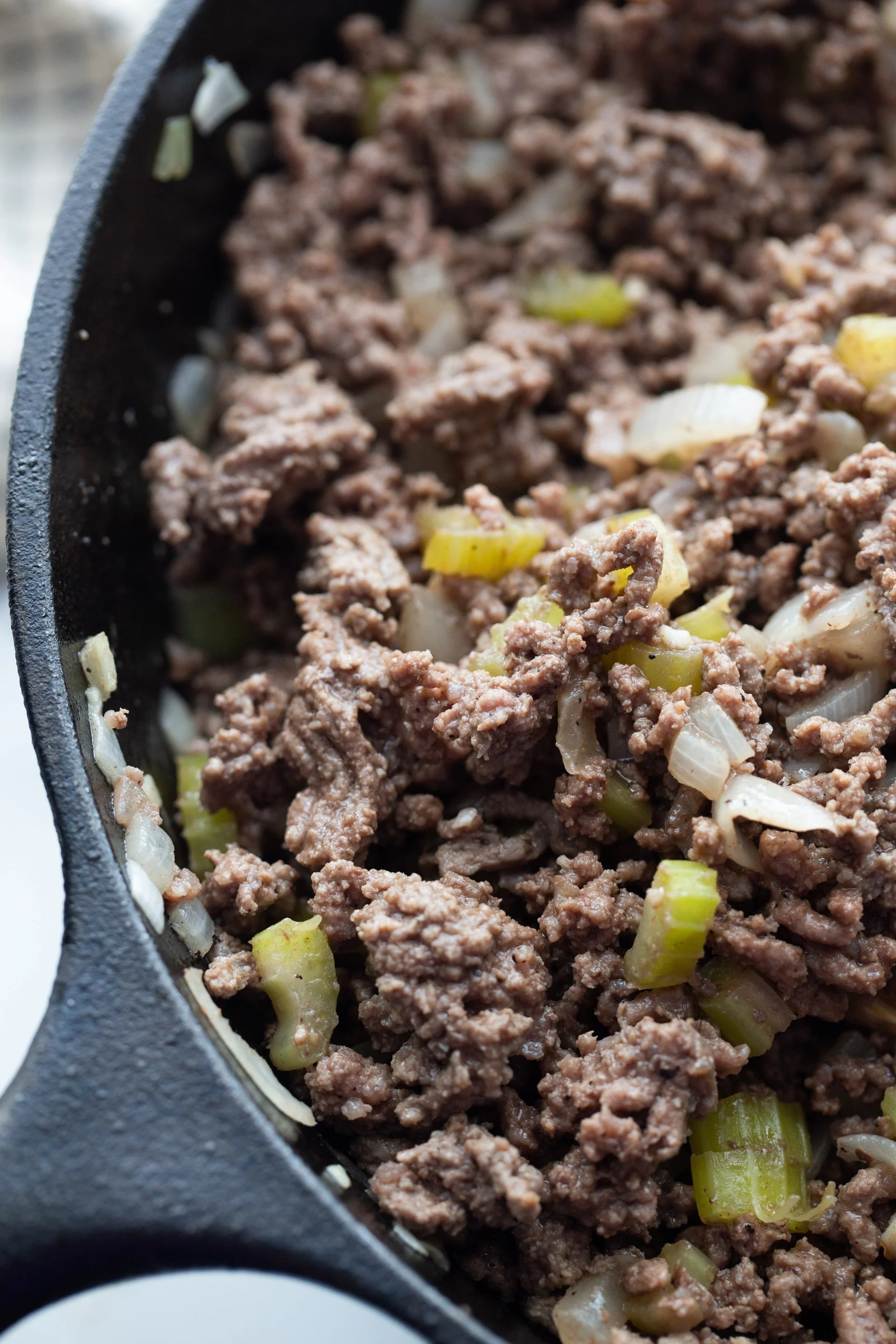 ground beef with onions and peppers in a skillet