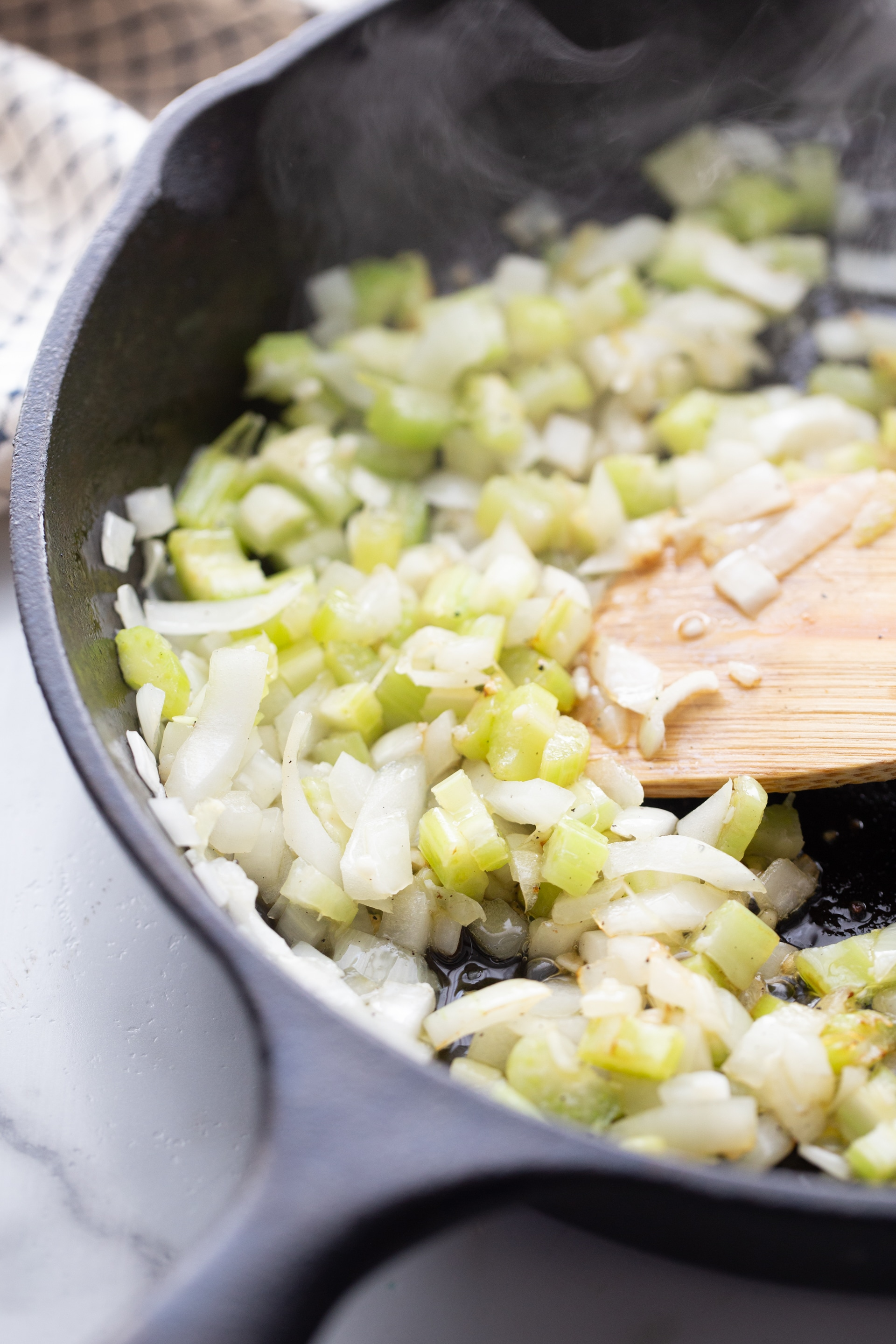 onions peppers sauteeing in a cast iron skillet