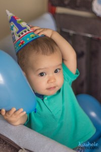 Image of little boy with birthday hat and balloons in his crib for Welcome to Kashele Photography Blog