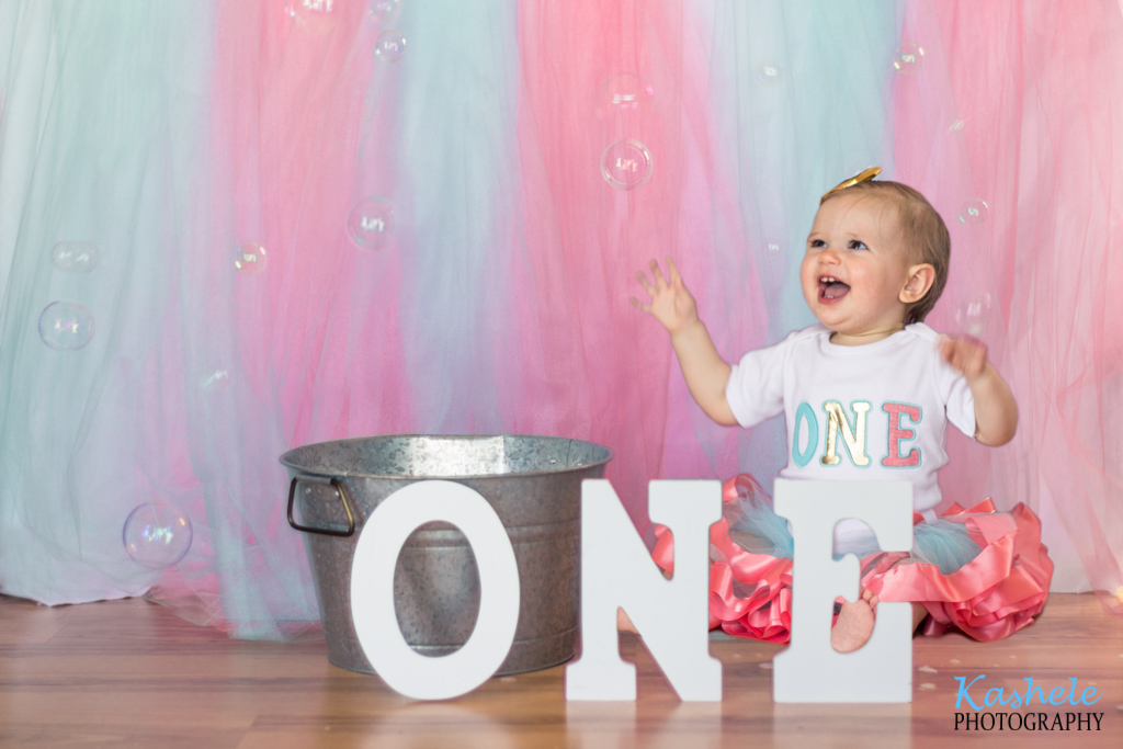 Miss Thomas' First Birthday Session: Image of baby wearing a pink tutu in a wash tub playing with bubbles