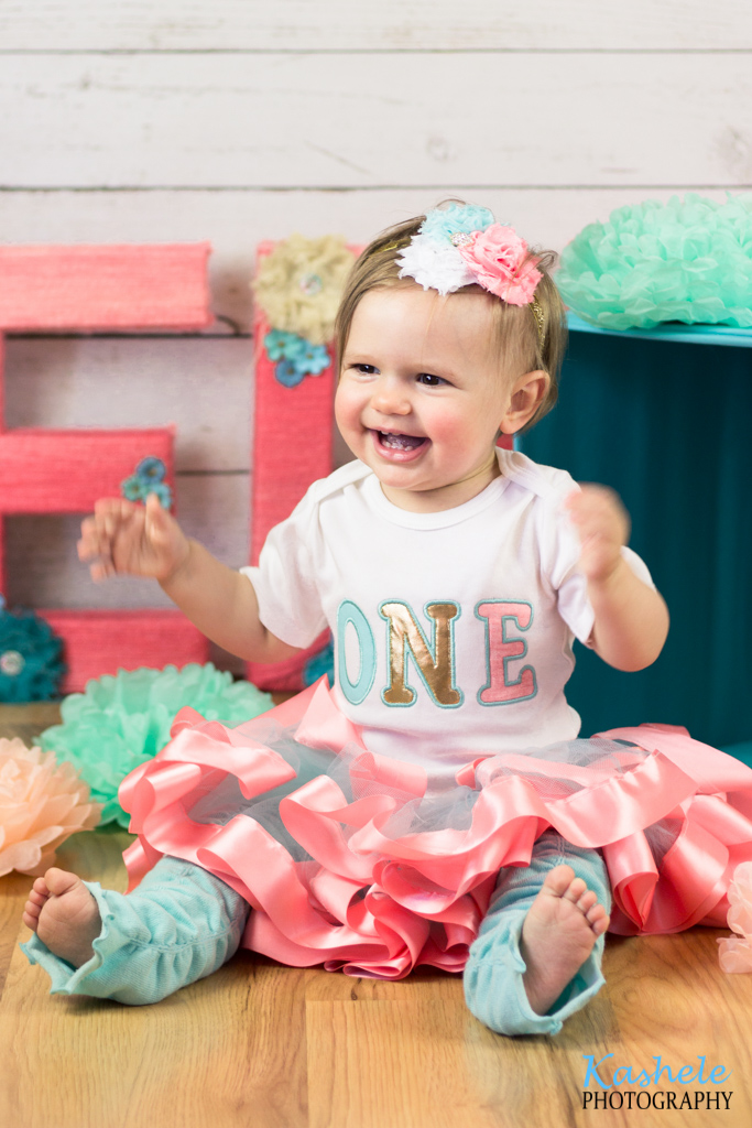 Miss Thomas' First Birthday Session: Baby wearing a pink tutu sitting near a present and pom poms