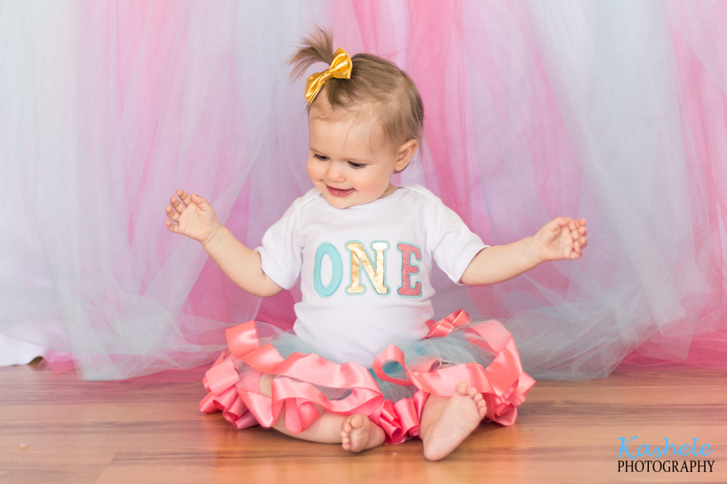 Miss Thomas' First Birthday Session: Image of baby wearing a pink tutu and golden bow