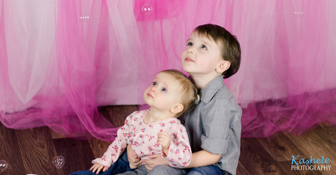 Image of brother and sister looking up at bubbles from Miss Hardy's First Birthday Session
