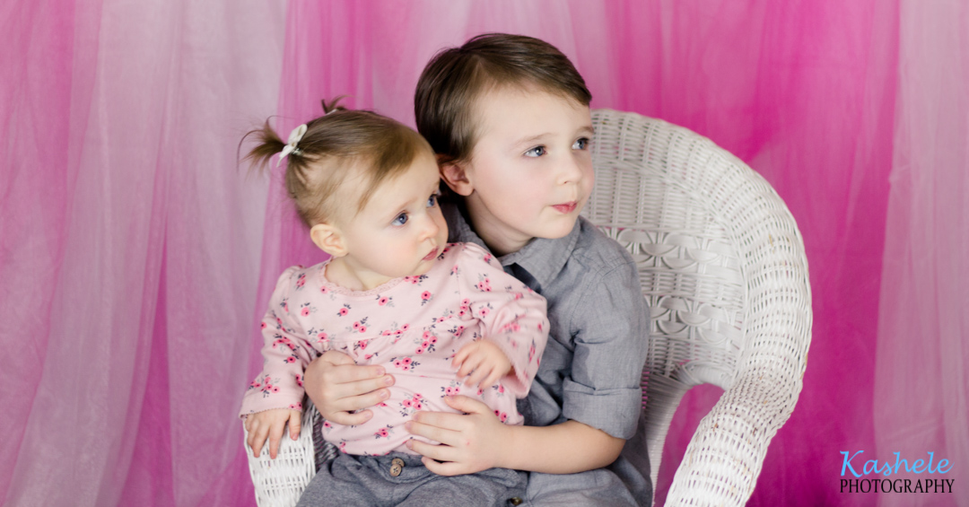 Image of brother and baby sister sitting in a wicker chair from Miss Hardy's First Birthday Session