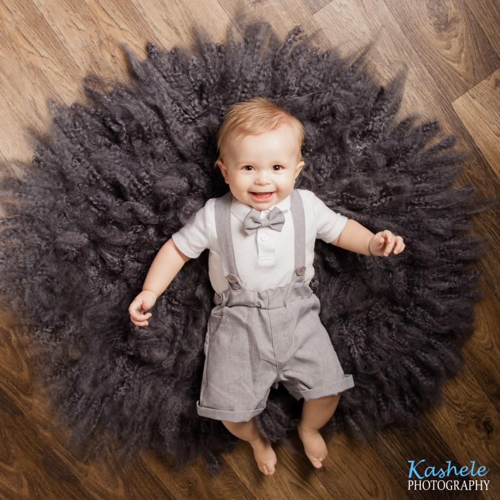 Milestone baby boy laying on gray rug on wood floor