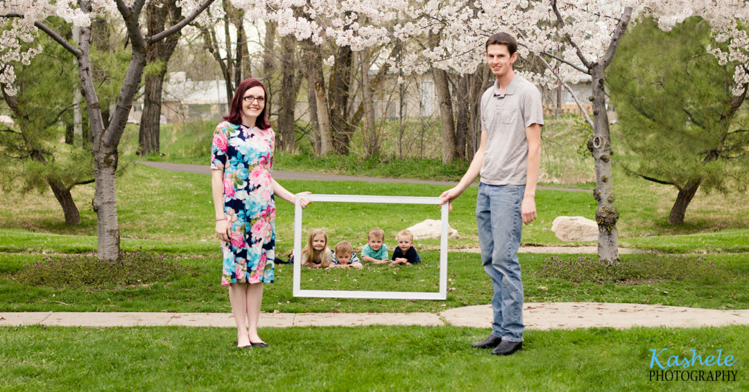 Swanson parents holding a frame with children inside