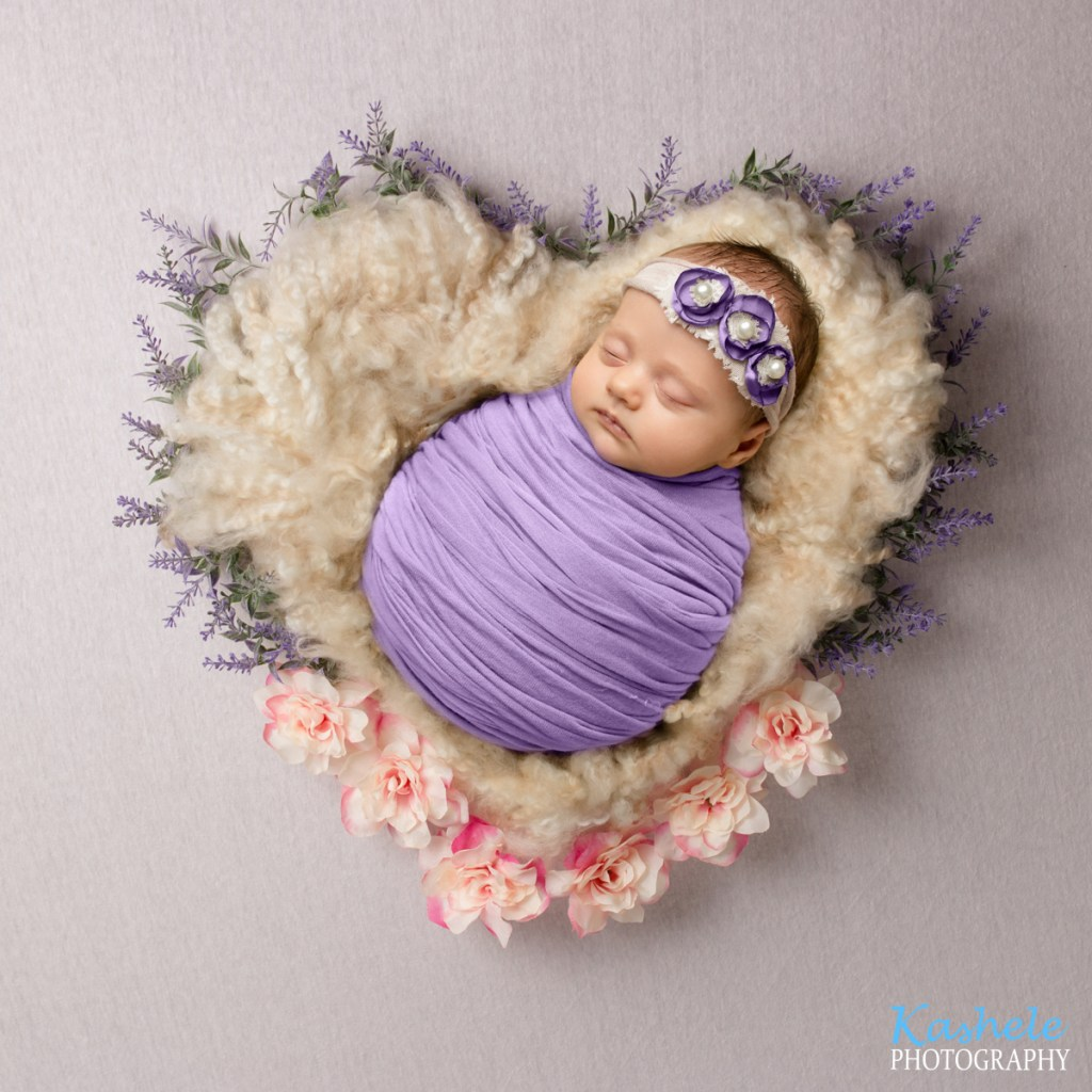 Image from Melissa's Newborn Session of baby girl on heart shaped fluff surrounded by flowers