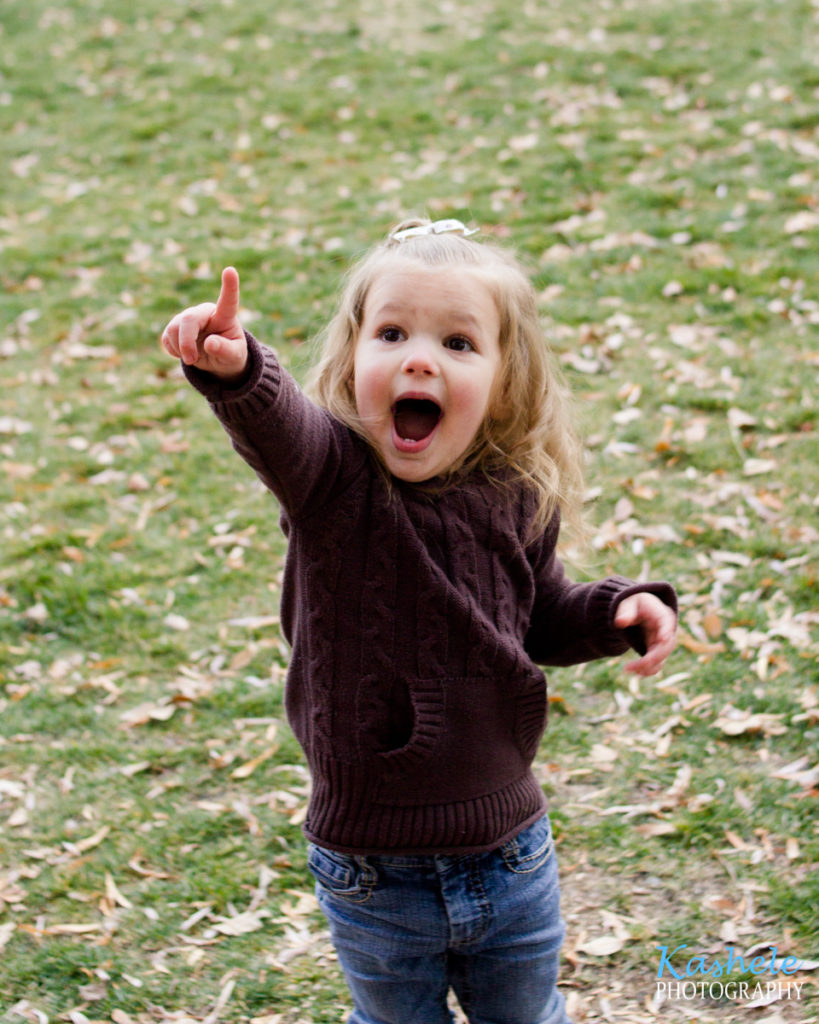 Little girl pointing up at the squirrel in the tree