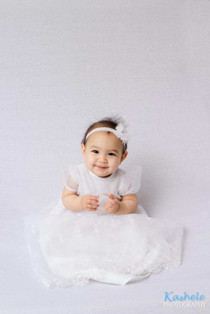 Smiling baby girl in white