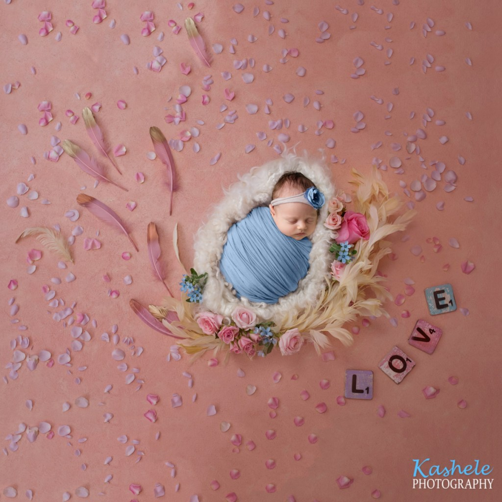 Image of baby girl on curly fluff surrounded by flowers