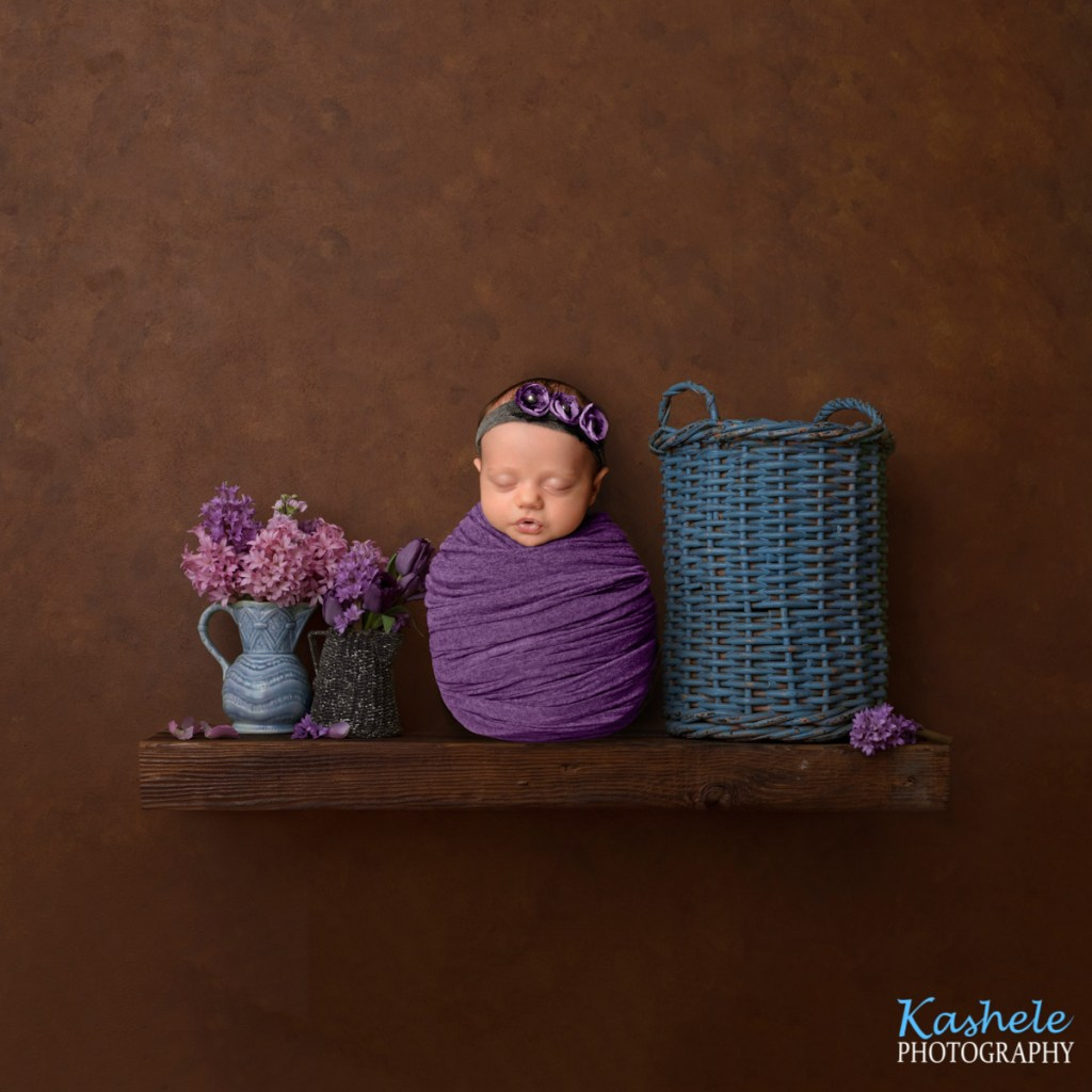 Image of baby girl sitting on a shelf beside flowers