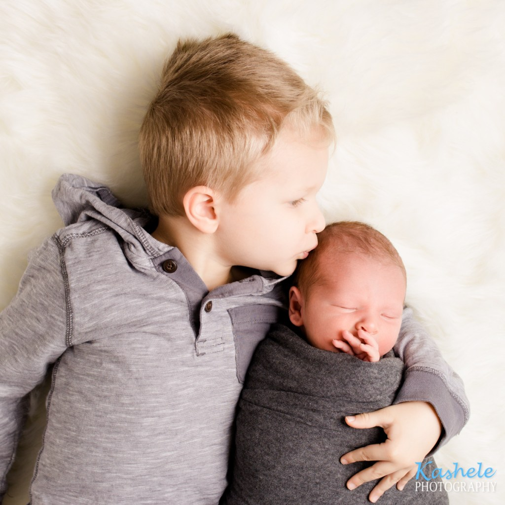 Photo of Big brother kissing baby brother