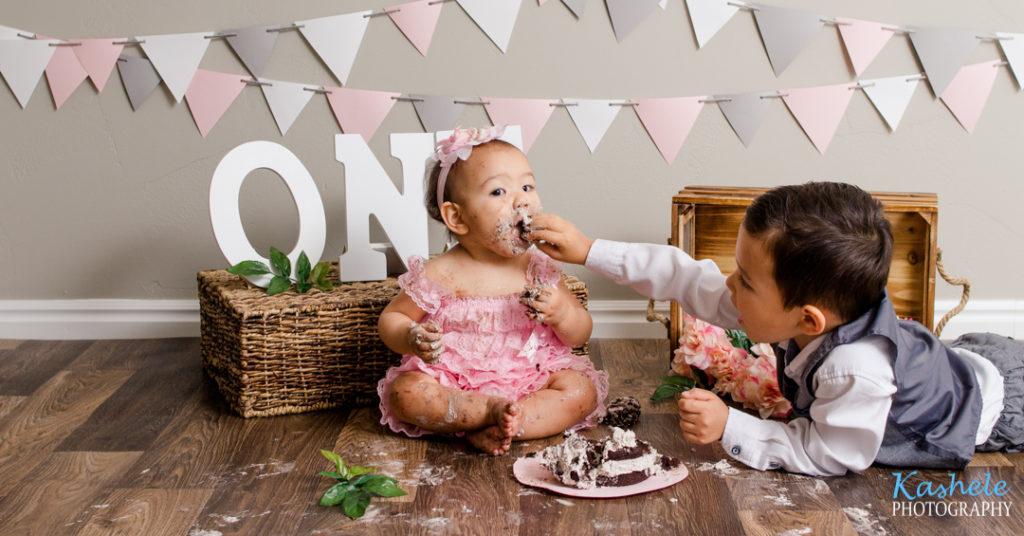 Brother feeding the birthday girl cake for Utah County Cake Smash