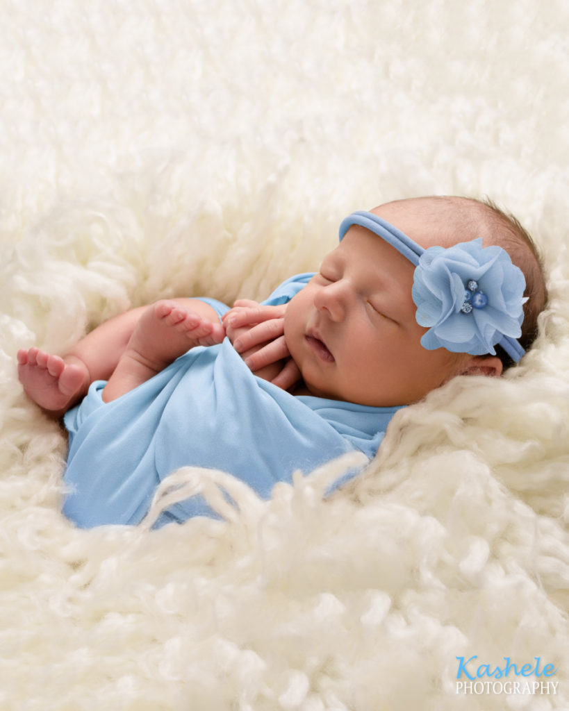 Baby in blue nestled in soft fluff for Eagle Mountain Newborn Photographer post