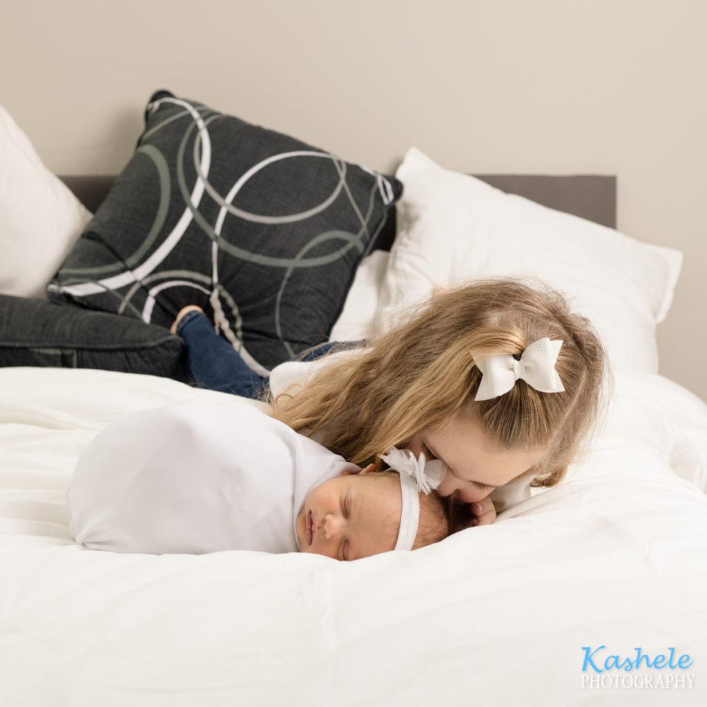 Image of big sister kissing baby sister