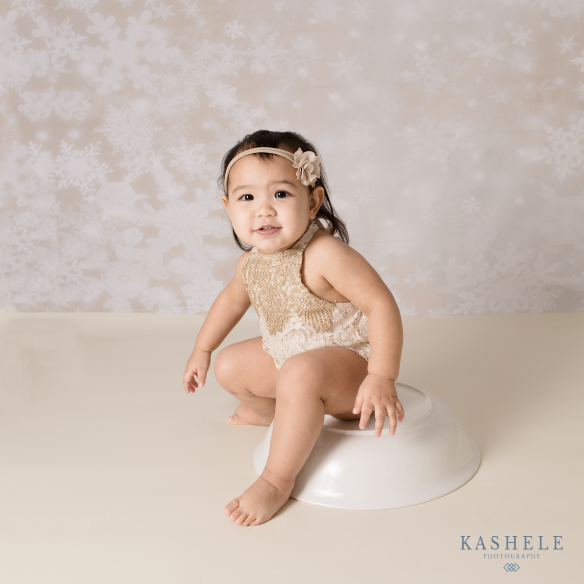 Little girl sitting on bowl for Why Schedule a Milestone Session post