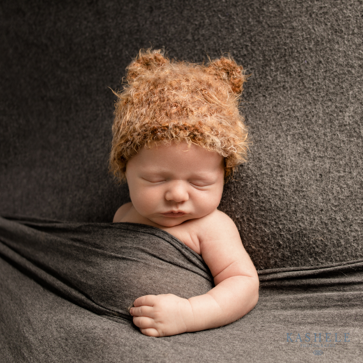 Image of baby boy in Huggalugs bear set tucked into bed