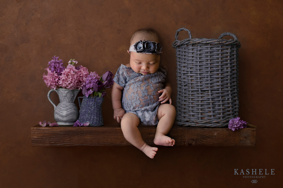 Smiling newborn baby girl sitting on a shelf