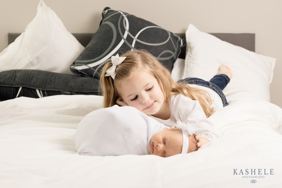 Portrait of baby with big sister on a bed