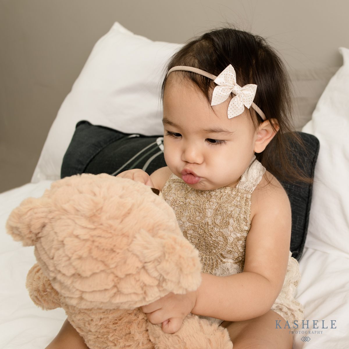 Little girl making a kissy face at her bear wearing a bow from mini sailor bow from Sweet Ellie Mae Shop