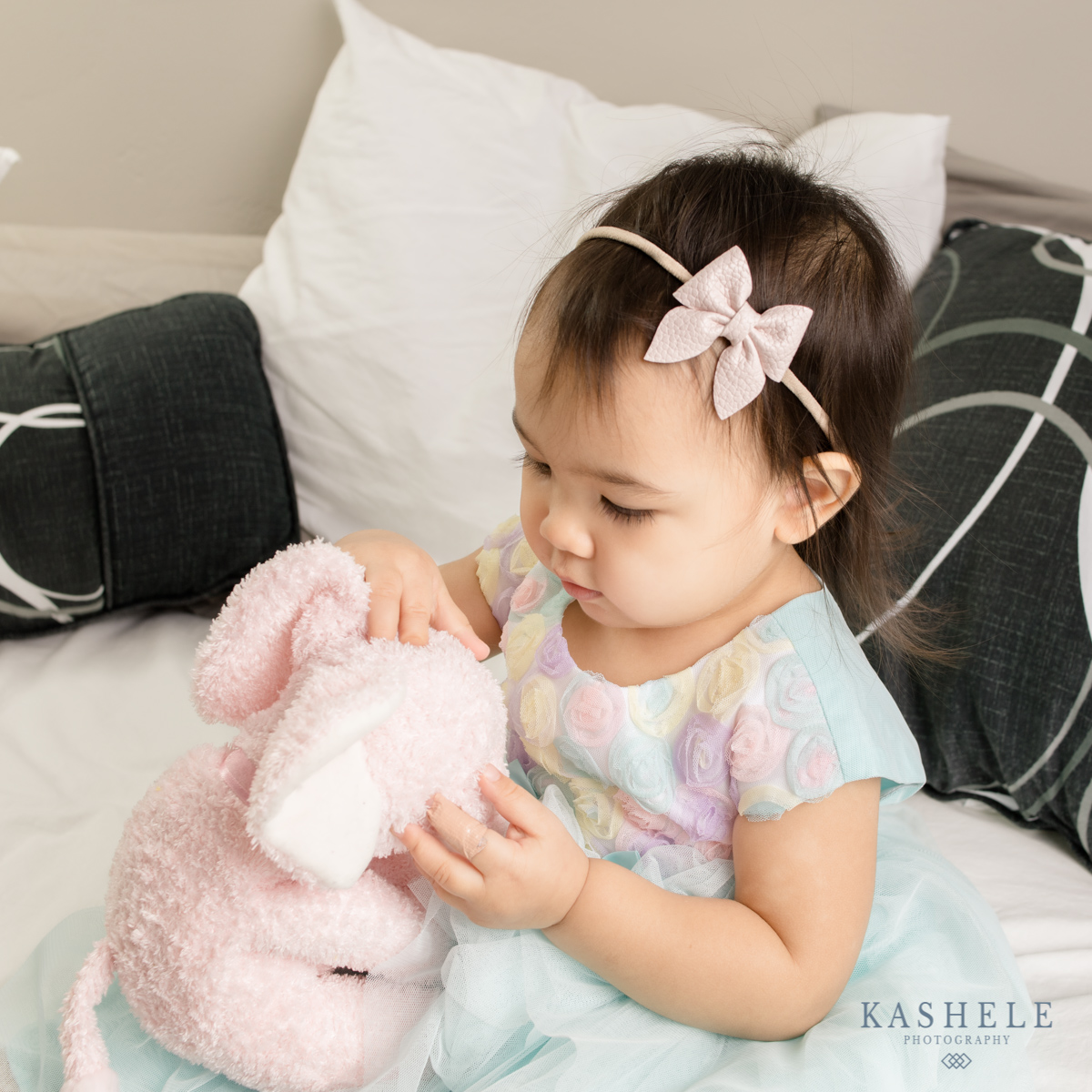 Little girl playing with an elephant stuffed animal