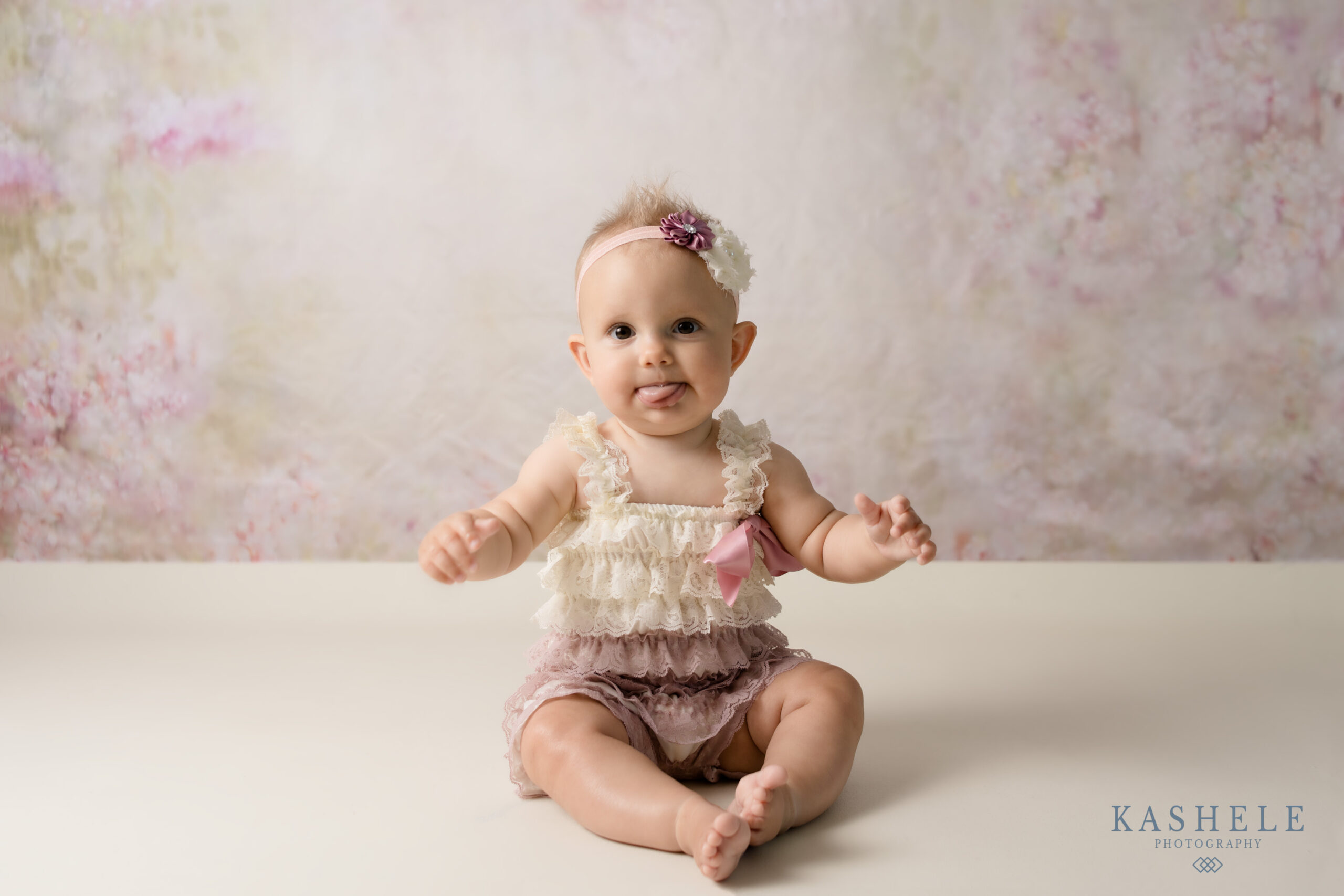 Little girl in lace romper with floral backdrop during milestone session