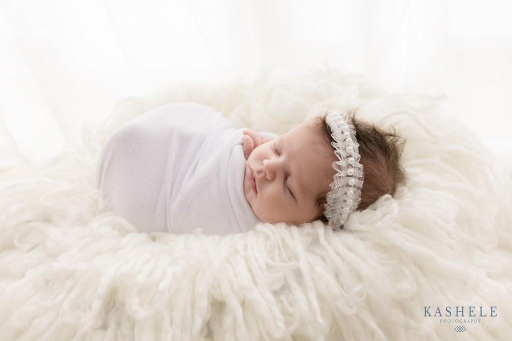 Newborn on white curly fluff