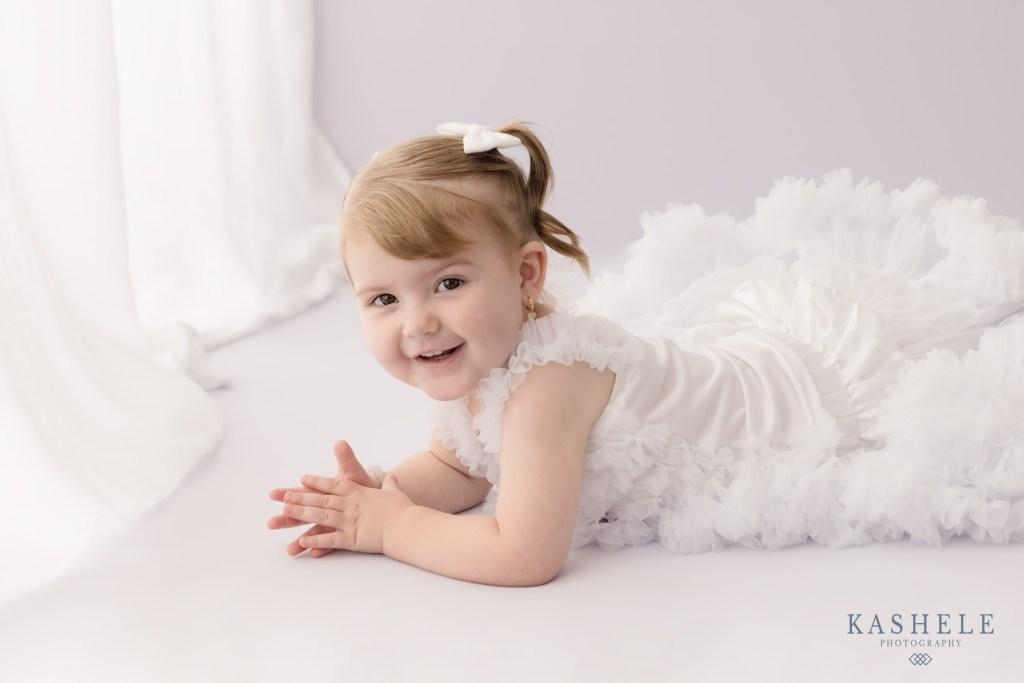 Little girl in white near a window