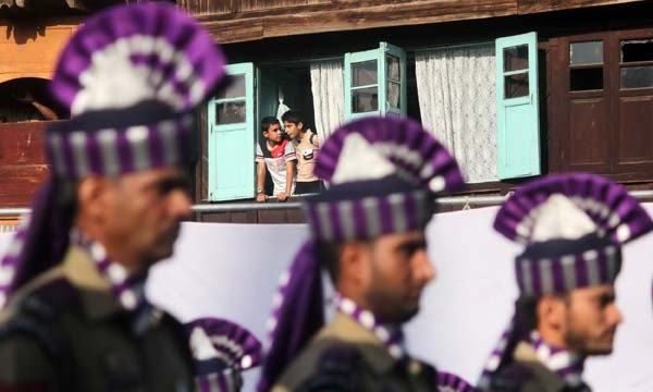 Window Watches: When all heads were down in homage, some curious kids appeared on window to have a glimpse of state honour. For the day, restrictions over area meant 'caging' in homes for locals in the area.
