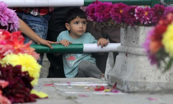 Witnessing Wreath: Far from the crowd, this kid witnessing Who's is Who in state of affairs of J&K. He made many unsuccessful attempts to cross that other side of divide, but barrier proved too robust for kid.