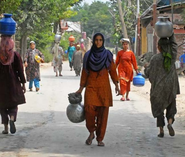 Treading on: Men, women, children in their school uniforms, newly married women with fresh henna on their hands, carrying large cans of all shapes and sizes rush to book their spot near the tap.