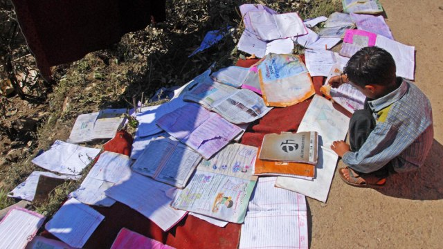 A kid sun drying his flood-affected school books.