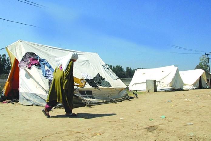 Old women walking in front of relief tent at Bund, Srinagar
