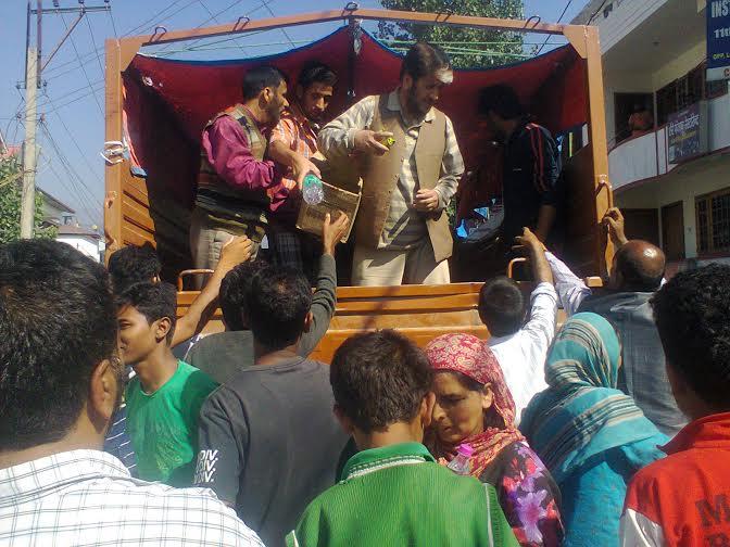 Hurriyat Conference JK chairman Shabir Shah distributing relief materials in Srinagar. Photo: KNS