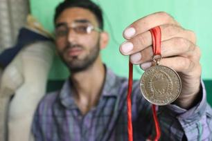 """""""These Images and awards were starkly illustrative of Javaid's love for cricket.""""; In pic Javaid displaying his medals."""