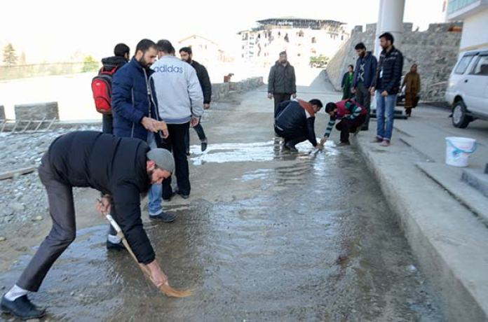 J&K EDI employees washing off blood stains a day after encounter ended.