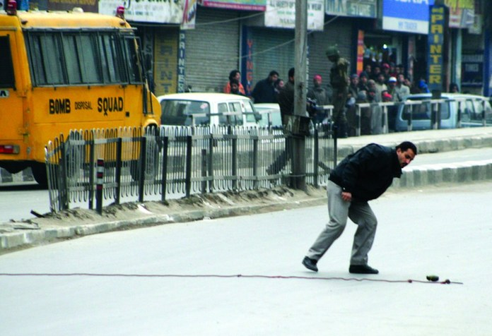 An expert of the bomb disposal squad prepares to defuse a grenade that was hurled towards a patrol of paramilitary and policemen, but failed to go off in Srinagar, on 22 January 2010. Security has been stepped up in Kashmir and other parts of India ahead of Republic Day ceremonies which falls on 26 January 2010, marking the day in 1950 when the country adopted its republican constitution photo by bilal bahadur