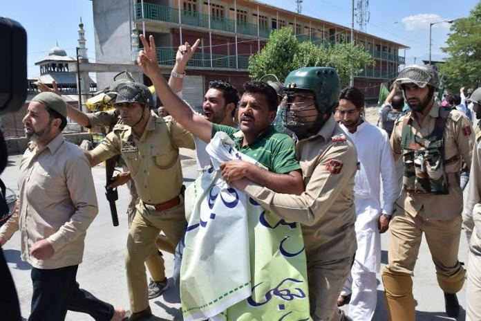 Police detain a Hurriyat Conference (m) activist on way to Eidgah on May 21, 2016.