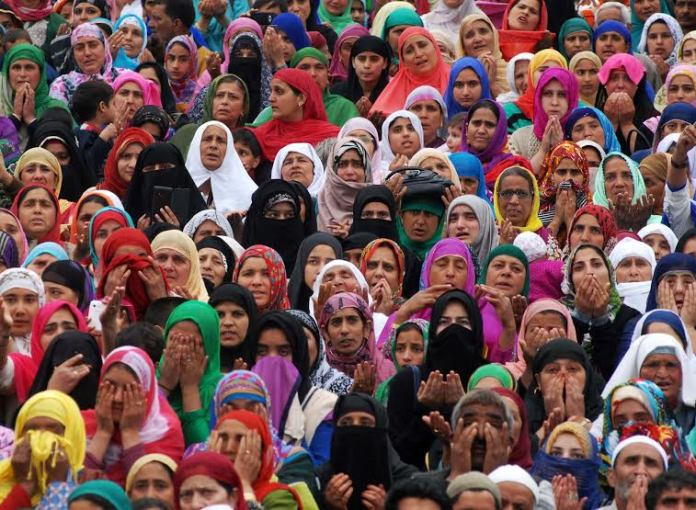 Kashmiri Muslim women raise their hands as they pray upon seeing a relic believed to be hair from the beard of Prophet Mohammed during Meeraj-un-Nabi celebrations at the Hazratbal shrine in Srinagar May 5, 2016. (KL Image: Bilal Bahadur)